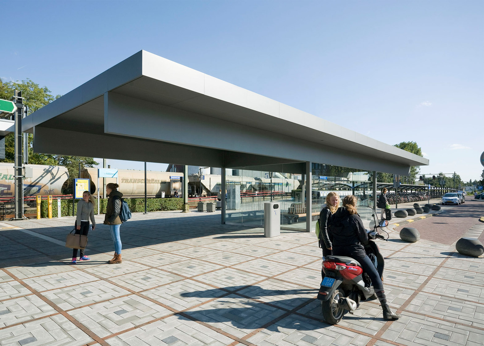 Huge steel roof oversails glazed waiting area at Barneveld Centrum station by NL Architects